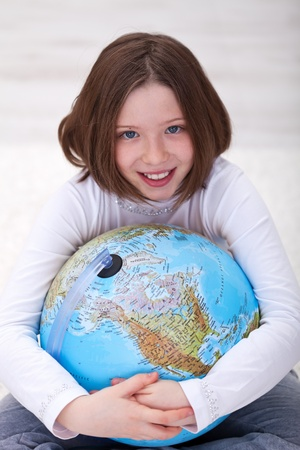 Young girl hugging earth globe - environment concept photo