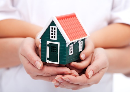 assure: Our home is protected - children and woman hands holding miniature house
