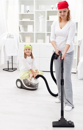 Woman and little girl tidy the room with vacuum cleaner photo