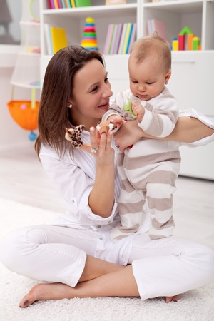 Mother and baby girl playing at home photo