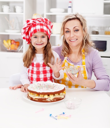 Making a cake for my birthday - little girl with mother in kitchen photo