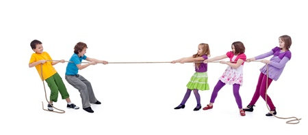 Kids playing tug of war - girls versus boys, isolated photo