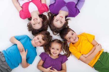 enfants qui rient: Cinq enfants heureux sur le sol, portant dans le cercle Banque d'images