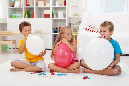 Kids blowing up large balloons indoors Stock Photo