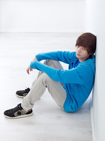 troubled teen: Moody teenager sitting by the wall on the floor