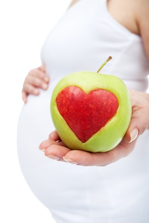 eating right: Eating right during pregnancy concept with apple and heart shape Stock Photo