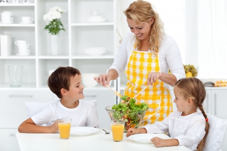 for kids: Healthy breakfast for happy life - mother serving kids with salad