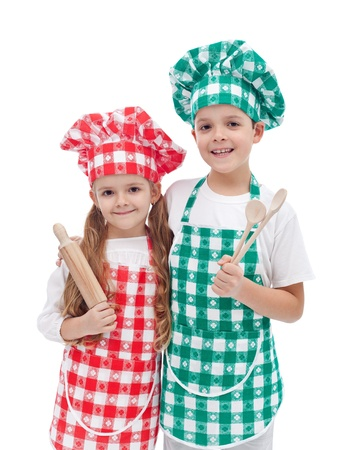 Happy kid chefs with hats and aprons holding cooking utensils - isolated photo