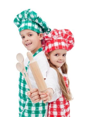 mujer hijos: Ni�os felices celebraci�n del chef de cocina y utensilios de madera sonriendo - aislados Foto de archivo