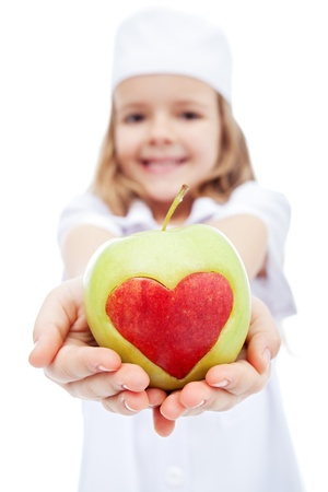 health care concept: Little girl dressed as nurse giving you an apple with heart - healthy life concept Stock Photo