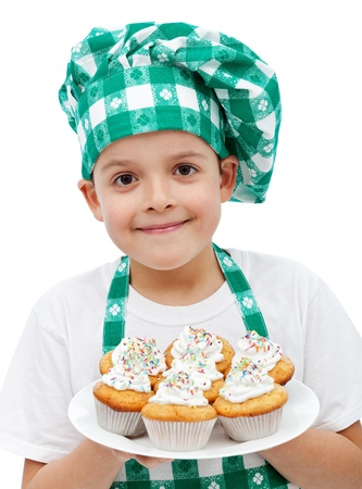 Happy smiling chef boy with a plate of muffins - isolated photo
