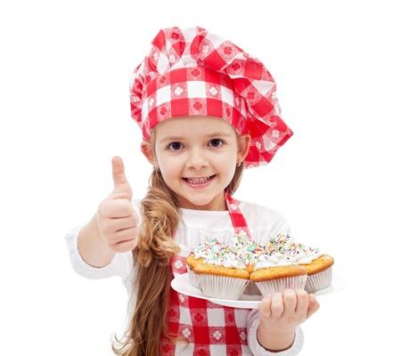 ni�os cocinando: Mis primeras magdalenas est�n listas - ni�a con sombrero de chef y galletas, aislados