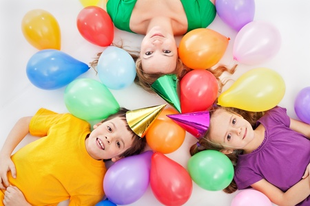 children party: Party kids and their mother laying among colorful balloons Stock Photo
