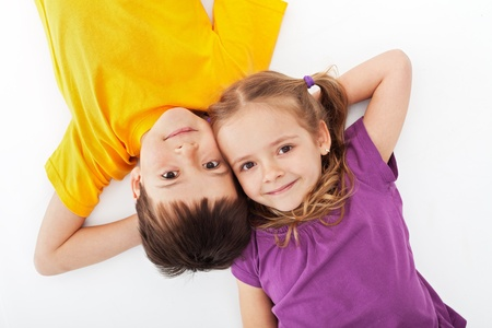 brother and sister: Happy kids relaxing laying on white - top view