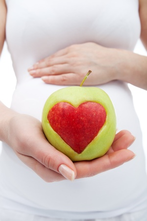 Healthy nutrition during pregnancy - woman holding apple in front of belly photo