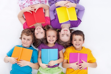child book: Happy kids laying on the floor holding books - the colorful world of reading Stock Photo