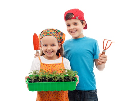 Happy spring gardening kids with seedlings and tools - isolated photo