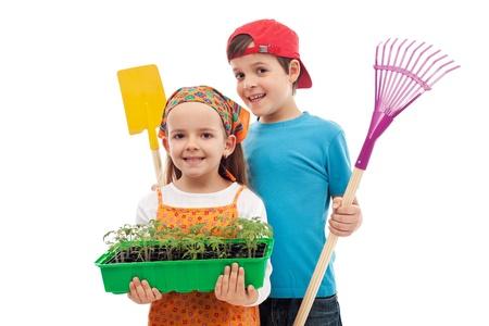 Niños ayudando: Los niños con plántulas de primavera y herramientas de jardinería - aislados