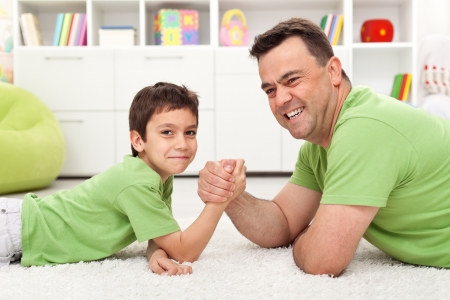 Happy father and son playing arm wrestling, lying on the floor photo