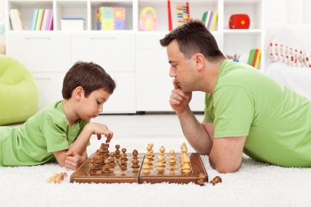 jugando ajedrez: Jugando al ajedrez con el papá - niño y su padre en el hogar