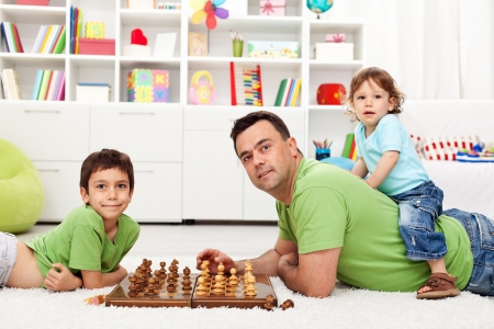 Father playing with his children - chess and piggyback at the same time photo