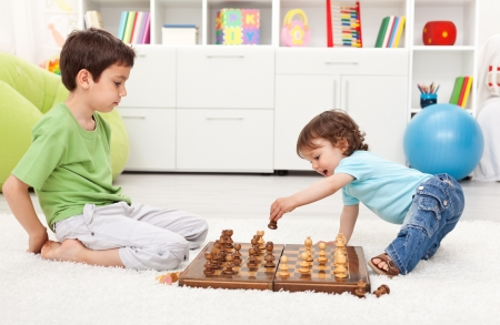 Small kids playing chess in their room photo