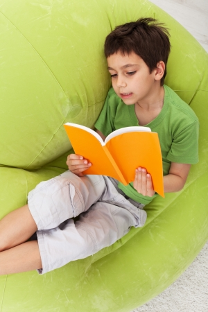 boy book: Boy practice reading relaxing on inflatable armchair Stock Photo