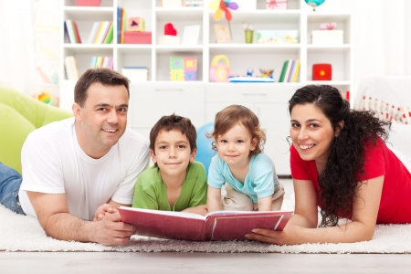 two story: Young happy family with two kids reading a story book - laying on the floor Stock Photo