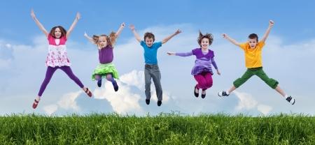boy jumping: Los ni�os felices que saltan en el campo de la primavera
