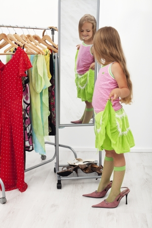 looking in mirror: Little girl trying on large shoes standing in front of mirror