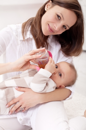Baby girl held by her mother - drinking from nursing bottle Stock Photo - 14304628
