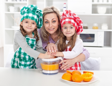 Woman and kids making fresh fruit juice - dressed as chefs in the kitchen photo