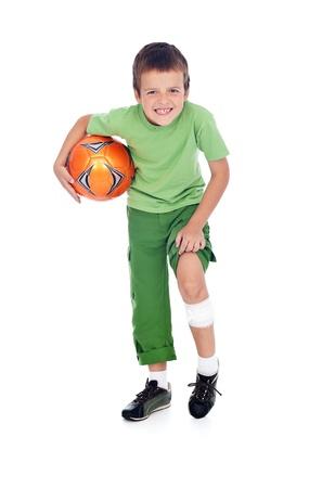 Boy with bandage on injured leg holding soccer ball - isolated photo