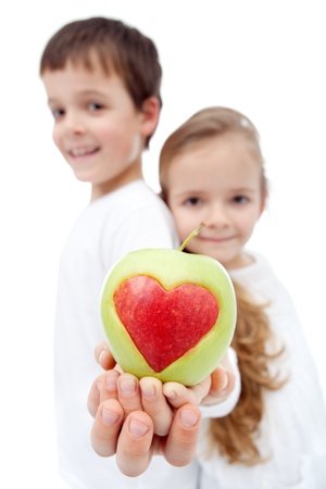 Healthy eating kids concept - children holding apple with heart sign photo