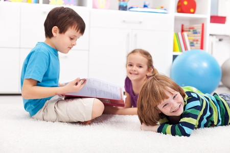 Kids reading a book and having fun together photo