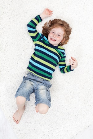 Happy little boy having fun laughing on the floor - top view Stock Photo - 14304661