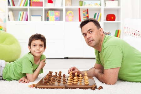 Father and son playing chess - family spending time together photo