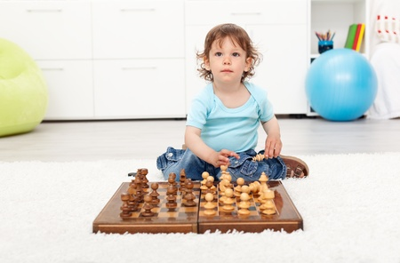 jugando ajedrez: Niño niño pequeño con tablero de ajedrez sentados en el suelo Foto de archivo