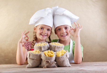 Kids with chef hats and pasta varieties in burlap bags- traditional food photo
