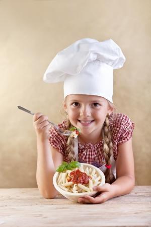 cocinero italiano: Little Chef comer pasta con salsa de tomate y albahaca - apoy�ndose en la mesa de madera vieja Foto de archivo