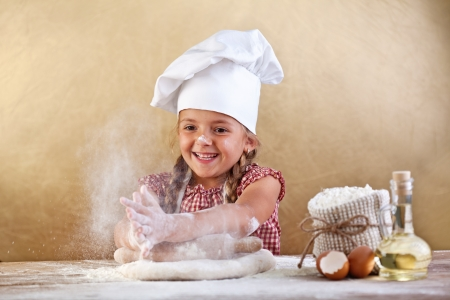 Making the dough for pizza is fun - little chef playing with flour