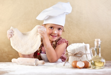 Little girl making pizza or pasta dough smeary with flour photo