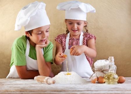 haciendo pan: Los ni�os con sombreros de chef que prepara una masa de pastel o pizza - romper los huevos en el mont�n de harina