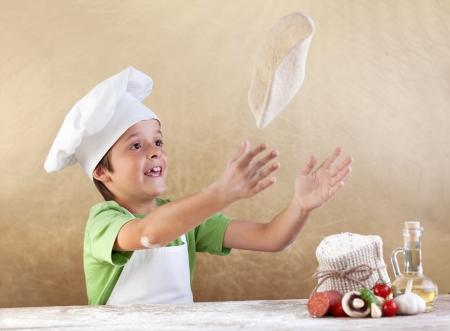 Chłopiec w kapeluszu kucharz przygotowuje ciasto do pizzy - ugniatania i rozciągania