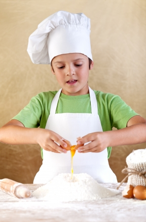 children cooking: Boy with chef hat preparing the dough - breaking the eggs in the flour pile