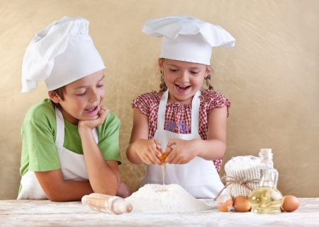 making fun: Kids preparing the dough for a cookie, pizza or pasta - having fun breaking the eggs Stock Photo