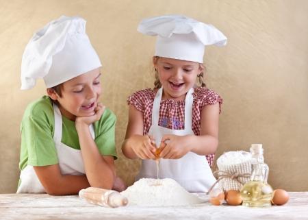 haciendo pan: Los ni�os la preparaci�n de la masa de una galleta, la pizza o la pasta - de haber divertido romper los huevos