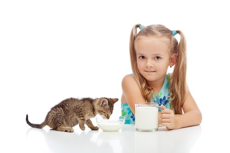 A little fresh milk for the little ones - girl and her kitten drinking, isolated photo