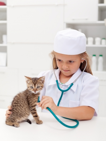 Little girl playing at the veterinary - consulting her little kitten photo