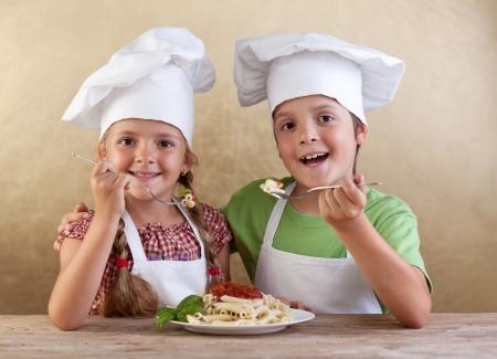 makarony: Szczęśliwe zdrowe dzieci z czapkami kucharz jedzenia świeżego makaronu - Kuchnia włoska koncepcja